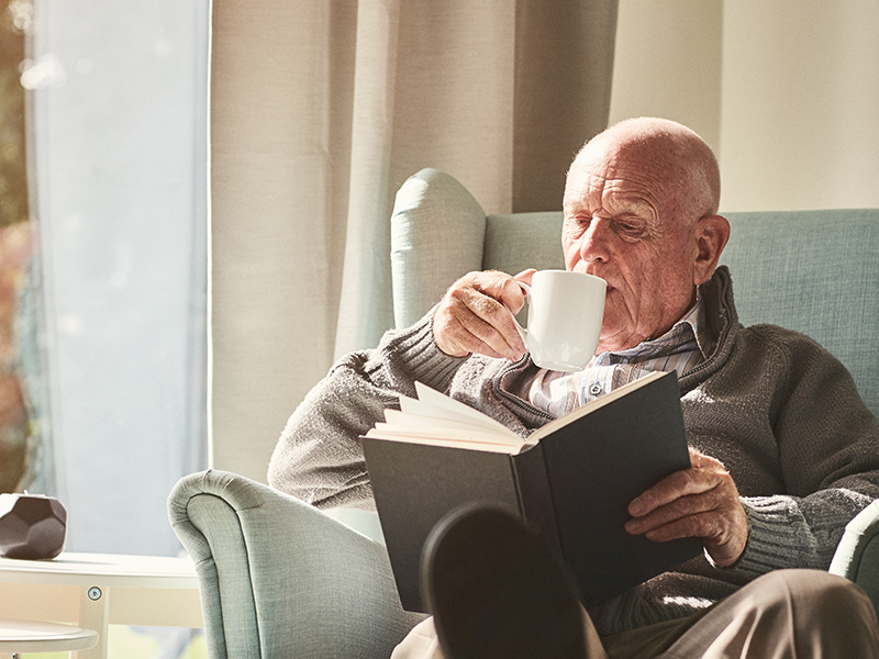 elderly sipping coffee and reading a book